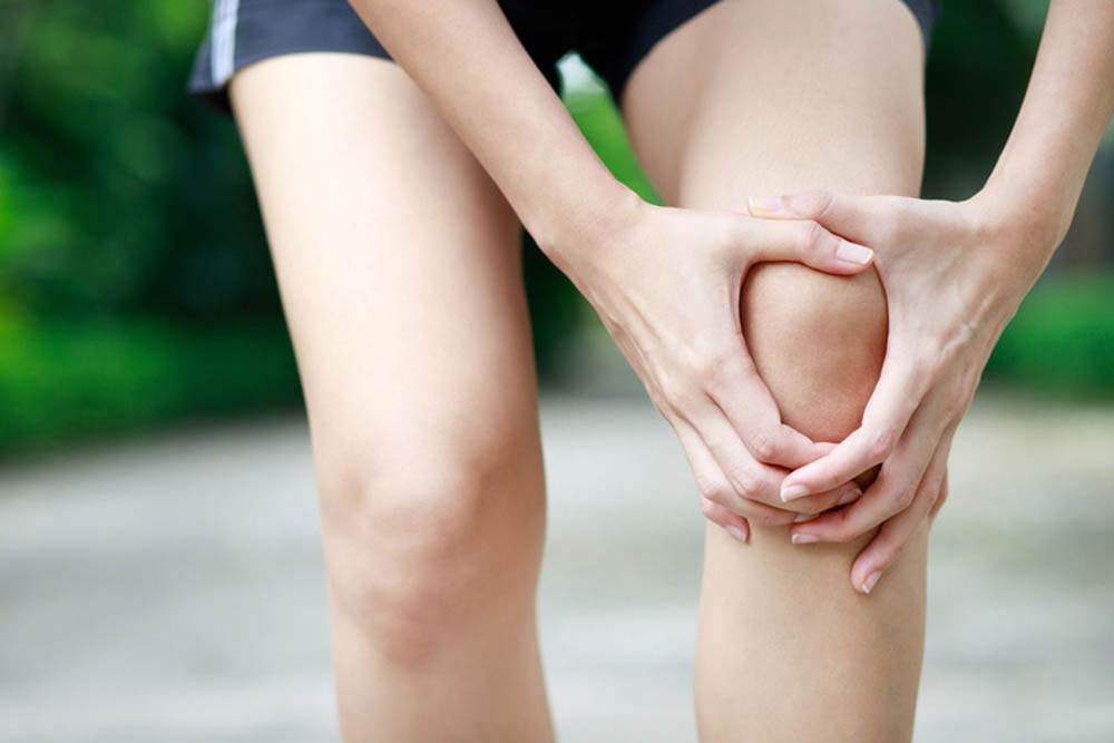 A person holds their sore knee.