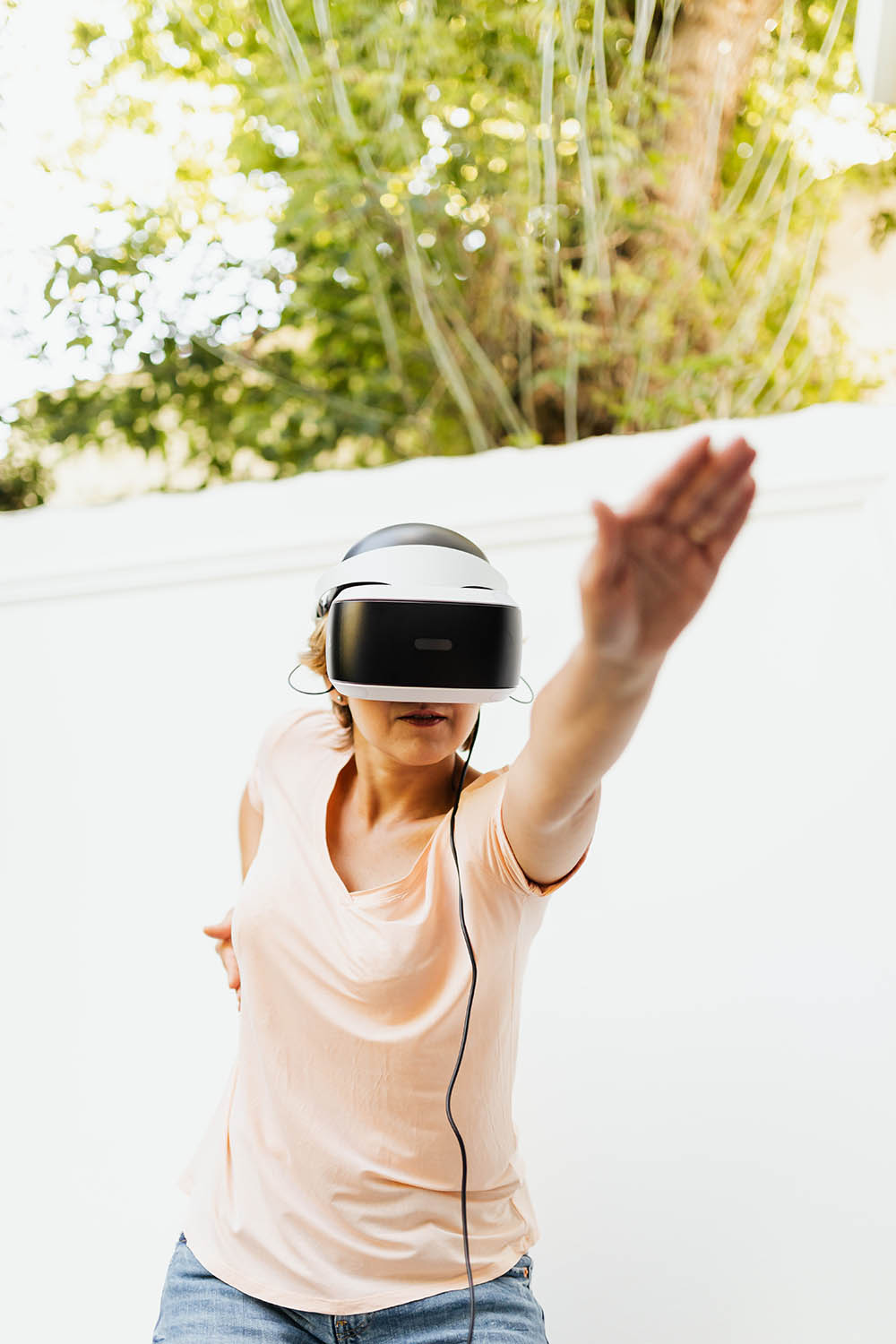 Person doing a yoga pose while wearing a virtual reality headset.