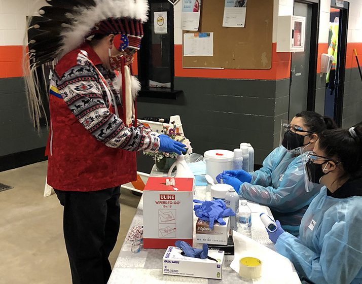 Chief David Monias of Pimicikamak Cree Nation checks in to be vaccinated at Cross Lake Arena, which served as a centre for immunizing the community.